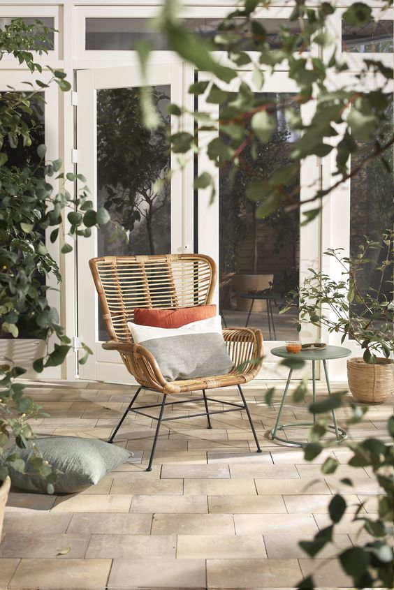a cool rattan chair styled with soft pillows, with a side table and some greenery around is a lovely piece for outdoors