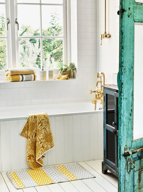 a lovely bathroom with pretty bright textiles   towels and a rug with a sunny yellow touch is welcoming