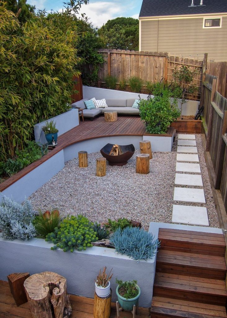a small and welcoming backyard with a fire pit zone and tree stumps with growing plants and trees, with a raised sitting zone with a sofa
