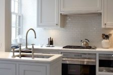 18 an elegant creamy kitchen with shaker style cabinets, a white subway tile backsplash and a hidden hood that looks like a cabinet