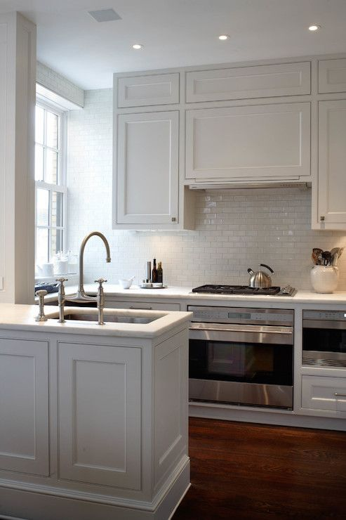 an elegant creamy kitchen with shaker style cabinets, a white subway tile backsplash and a hidden hood that looks like a cabinet