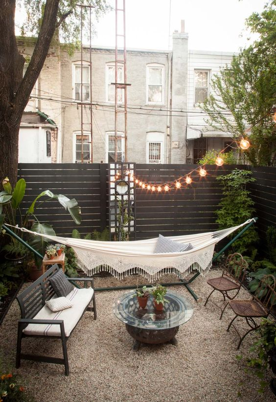 a cool outdoor space with a black planked fence, a hammock on a stand, outdoor furniture and a greenery around is fresh and bold