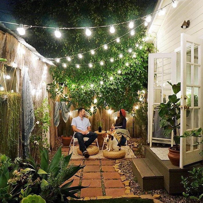 a small and welcoming backyard with tiles and pebbles on the ground, with cool chairs and jute poufs, with string lights and potted plants all over