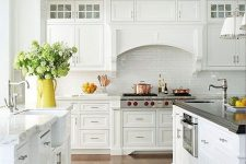 19 an elegant white cottage kitchen with a hidden hood, a white subway tile backsplash and silver touches here and there