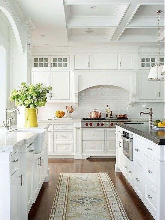 an elegant white cottage kitchen with a hidden hood, a white subway tile backsplash and silver touches here and there