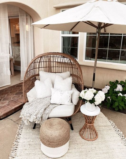a cozy outdoor nook with a rattan egg-shaped chair and pillows, an umbrella, a jute pouf, a mini side table with blooms