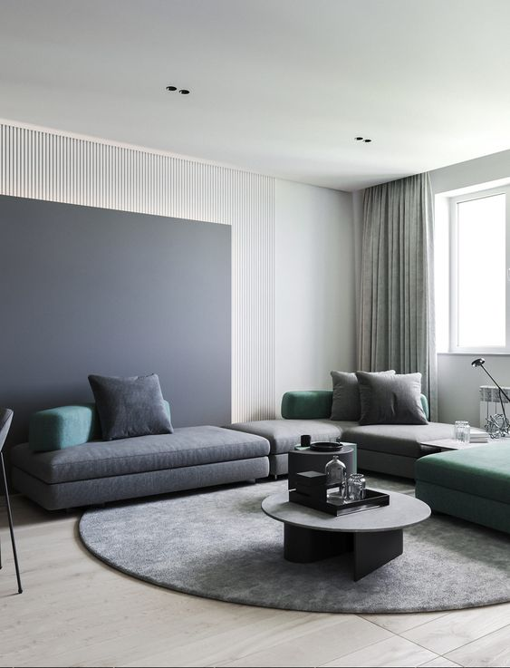 a minimalist living room spruced up with slate grey and green touches, furniture and accessories is a very chic space to be