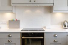 20 an eye-catchy grey kitchen with a white skinny tile backsplash, white countertops and a hood hidden inside a cabinet