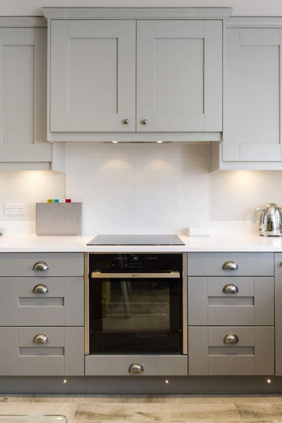 an eye-catchy grey kitchen with a white skinny tile backsplash, white countertops and a hood hidden inside a cabinet