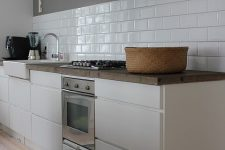 21 a beautiful Scandinavian kitchen with sleek white cabinets, a white subway tile backsplash and a grey hood that merges with the wall