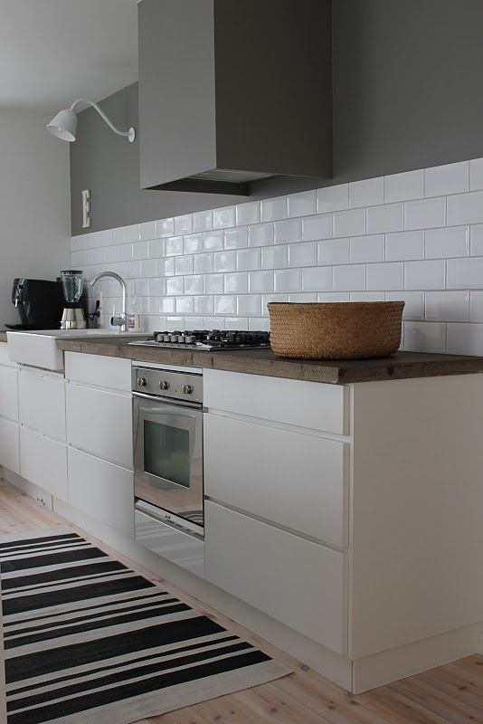 a beautiful Scandinavian kitchen with sleek white cabinets, a white subway tile backsplash and a grey hood that merges with the wall