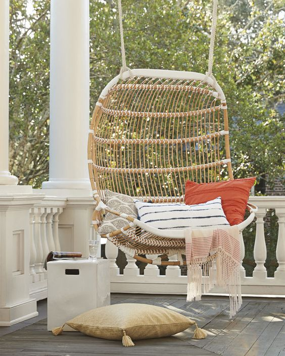 a double hanging rattan chair with printed pillows and a pillow on the floor, a small side table compose a cool porch for relaxing