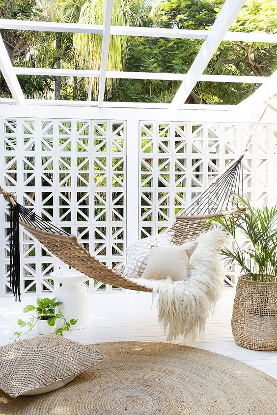 a dreamy outdoor space with a white pergola, a woven hammock with pillows, jute accessories and potted greenery is chic and beautiful