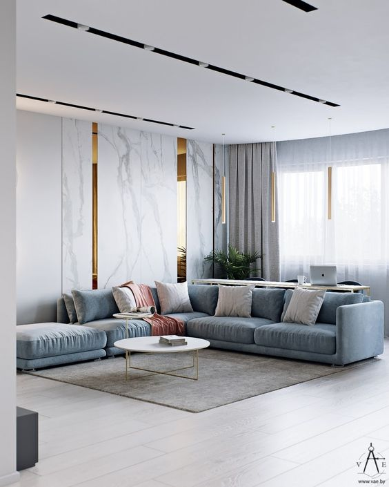 a minimalist living room with a blue sectional, hidden storage units with marble panels and neutral textiles all over