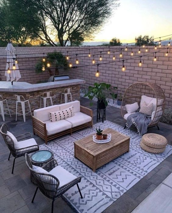 a small backyard turned into an entertainment zone, with a bar, a sitting zone with rattan furniture and string lights is very cozy