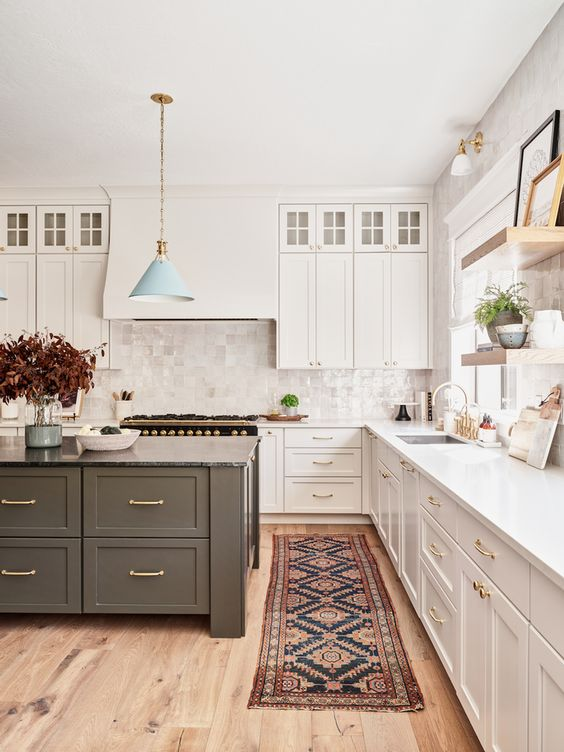 a chic farmhouse kitchen with elegant white cabinetry, a grey kitchen island, a hidden hood on the wall and a white tile backsplash