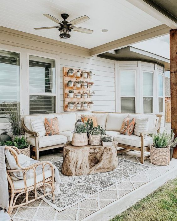 a farmhouse porch with a wooden corner sofa, a rattan chair, printed pillows, blankets and layered rugs and some potted greenery