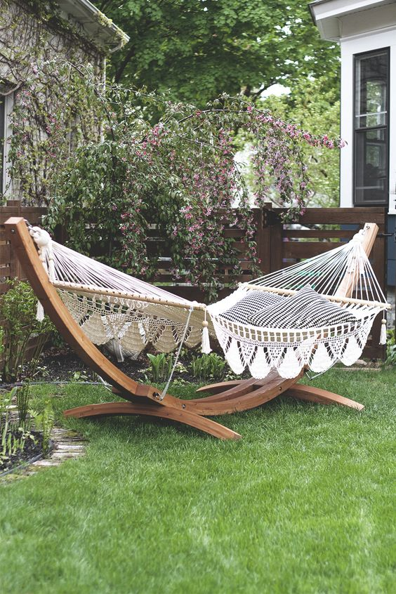 a garden space with a large hammock on a stand and printed pillows is a dreamy space to have a nap