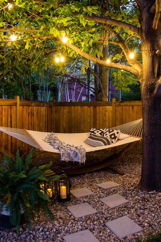 a small backyard with a hammock oasis, with some lanterns on the ground, ferns, string lights and printed pillows is a dreamy space