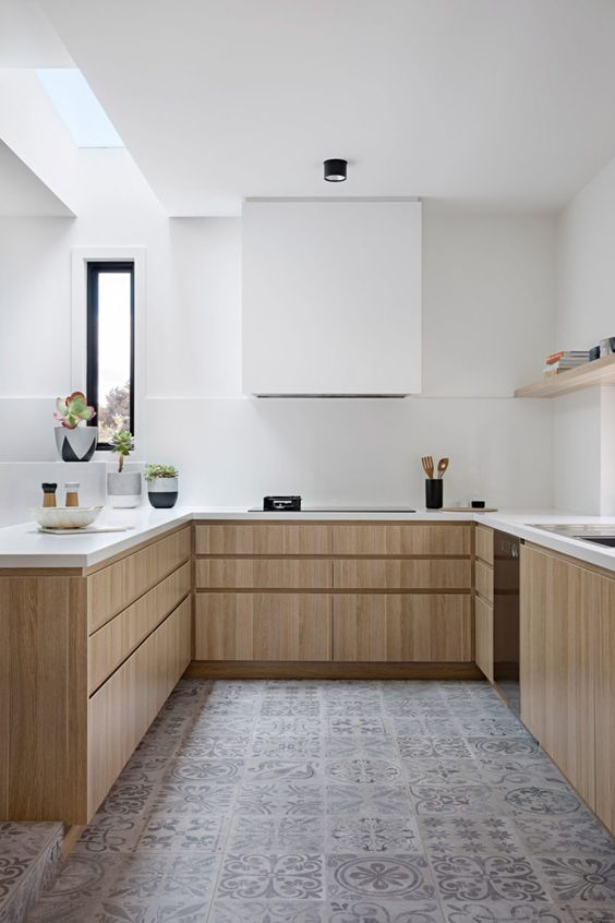 a chic minimalist kitchen with light stained lower wooden cabinets, a white hood that merges with the wall and white countertops