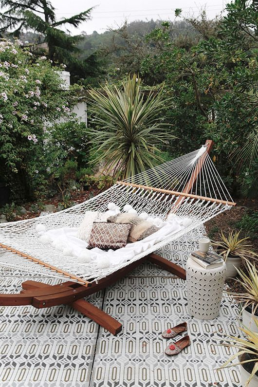 a gorgeous outdoor boho tropical space with a printed rug, a hammock on a stand, a laser cut side table and tropical plants around