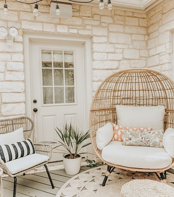 a lovely backporch with rattan chairs, a jute rug, a potted plant, some pillows and string lights over the space