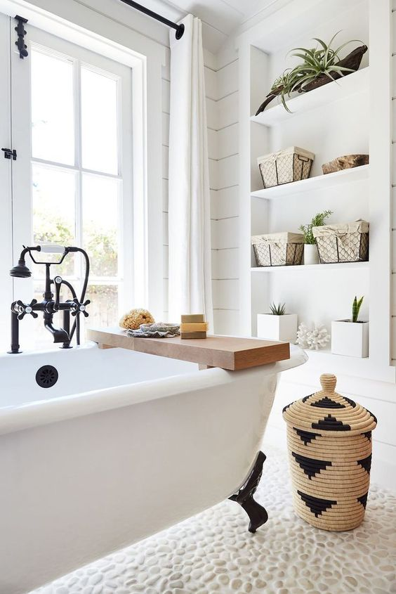 a lovely light filled bathroom with corals, potted plants, a basket for storage and some natural soaps feels like summer