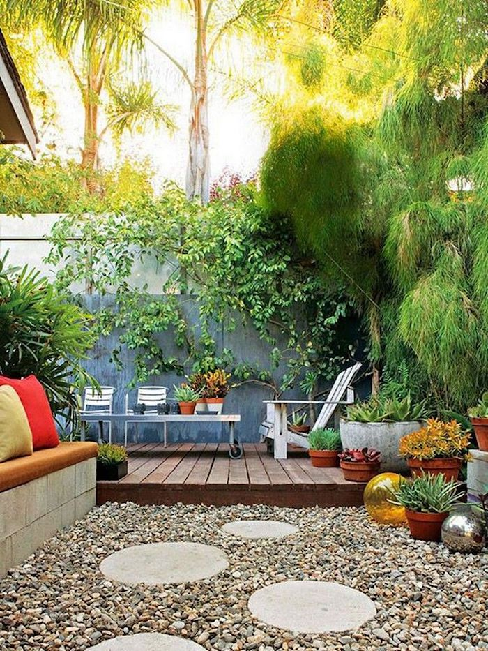 a small backyard with pebbles and a sitting zone with a built-in bench, lots of potted plants, a living wall and modern garden furniture