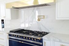 24 a glam and refined kitchen with white cabinets, a white marble backsplash and countertops, a hood covered with the same marble and with a gold panel