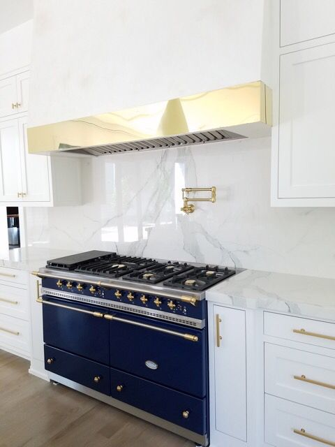 a glam and refined kitchen with white cabinets, a white marble backsplash and countertops, a hood covered with the same marble and with a gold panel