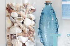 24 a glass vase with seashells, a blue fish-shaped bottle and some starfish will give your bathroom a coastal feel