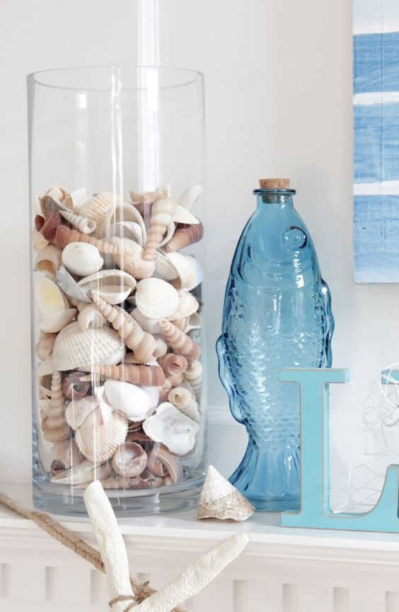 a glass vase with seashells, a blue fish shaped bottle and some starfish will give your bathroom a coastal feel