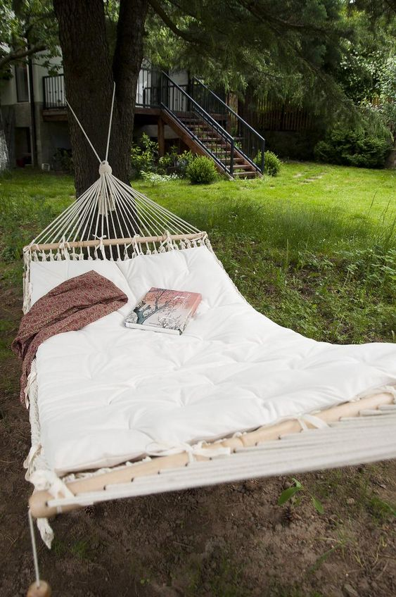 a large hammock attached to the trees, with a mattress and a blanket is an ideal space for reading and relaxing