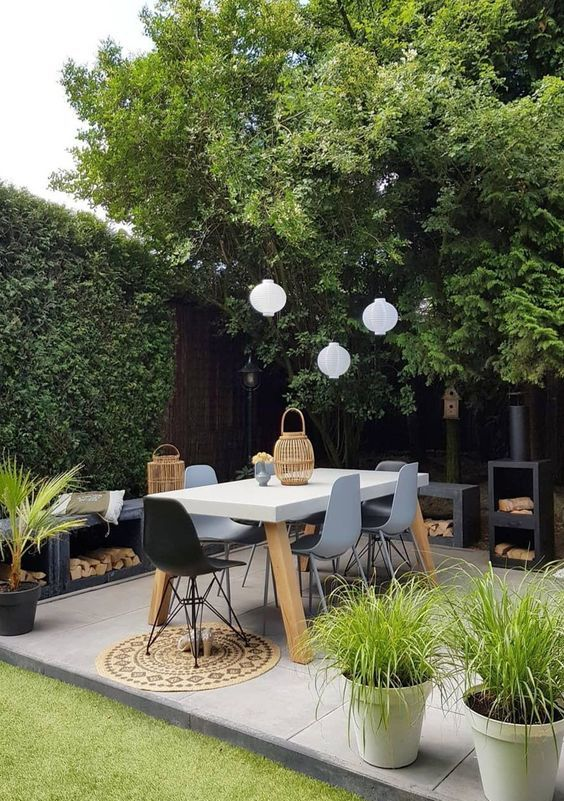 a small contemporary backyard with a hearth, with cool contemporary furniture, pendant lamps and potted plants is chic