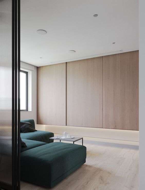 a small minimalist living room with light-stained plywood panels, a dark green sectional, a small coffee table and sliding doors