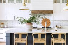 25 a lovely coastal farmhouse kitchen with white cabinets, a navy kitchen island, a white skinny tile backsplash and a hood covered with planked wood