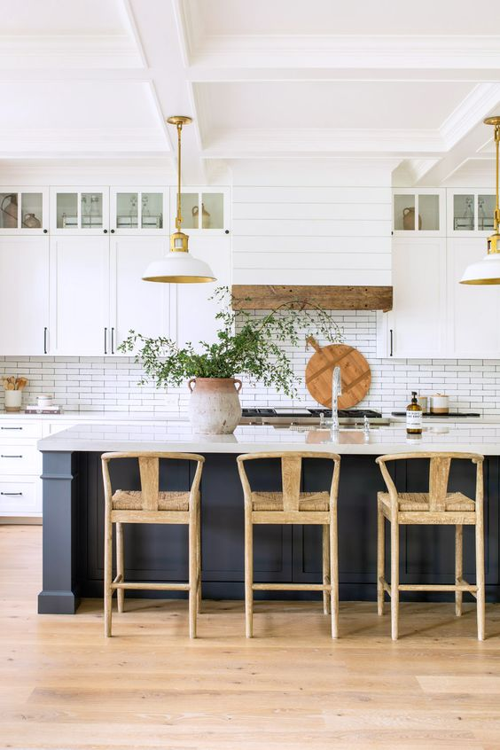 a lovely coastal farmhouse kitchen with white cabinets, a navy kitchen island, a white skinny tile backsplash and a hood covered with planked wood