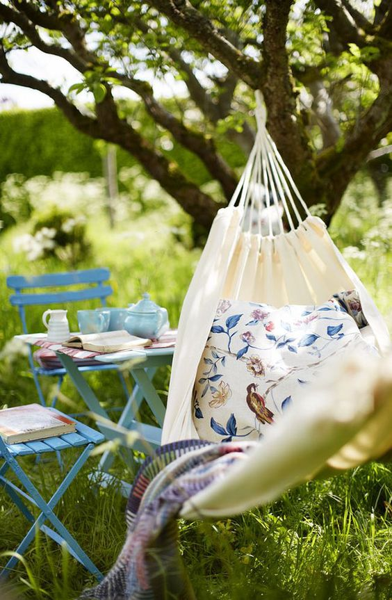 a lovely garden nook with a hammock with printed accessories, a blue outdoor furniture set and some blue porcelain