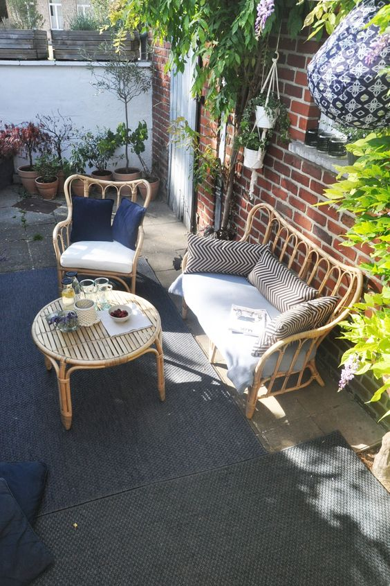 a lovely terrace with a red brick wall, rattan furniture, printed pillows and lots of potted greenery and blooms around