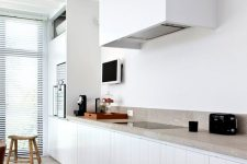 26 a lovely kitchen in white, with planked cabinets and a sleek white hood that merges with the wall, a grey stone countertop and a matching floor