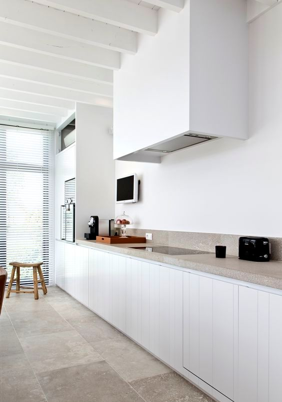 a lovely kitchen in white, with planked cabinets and a sleek white hood that merges with the wall, a grey stone countertop and a matching floor