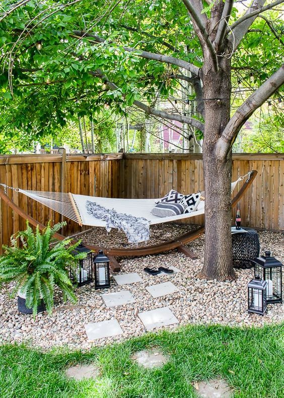 a lovely outdoor nook with a hammock on a stand placed under a tree, with potted ferns and some candle lanterns