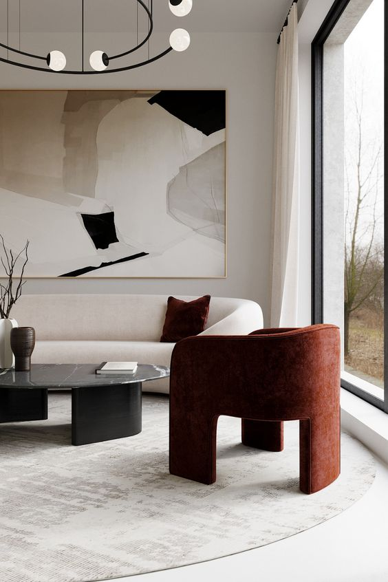 a sophisticated minimalist living room with lovely cruved furniture, a statement artwork, a burgundy chai and a black marble table