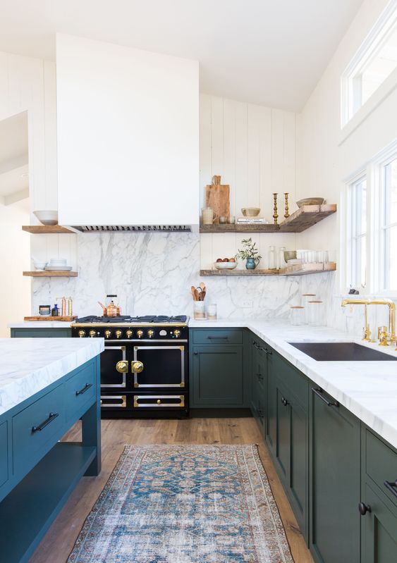 a lovely modern farmhouse kitchen with navy cabinets and a white hood that matches the wall, open shelves and marble countertops