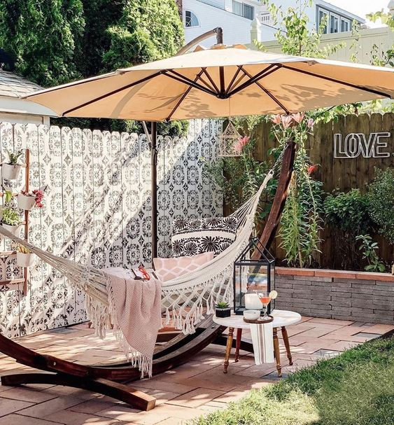 a lovely outdoor space with a tiled floor, a hammock on a stand with an umbrella, greenery and a painted fence