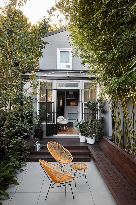 a small minimalist backyard with a dark stained deck and a tiled floor, with growing bamboo and plants and chic woven chairs and a table