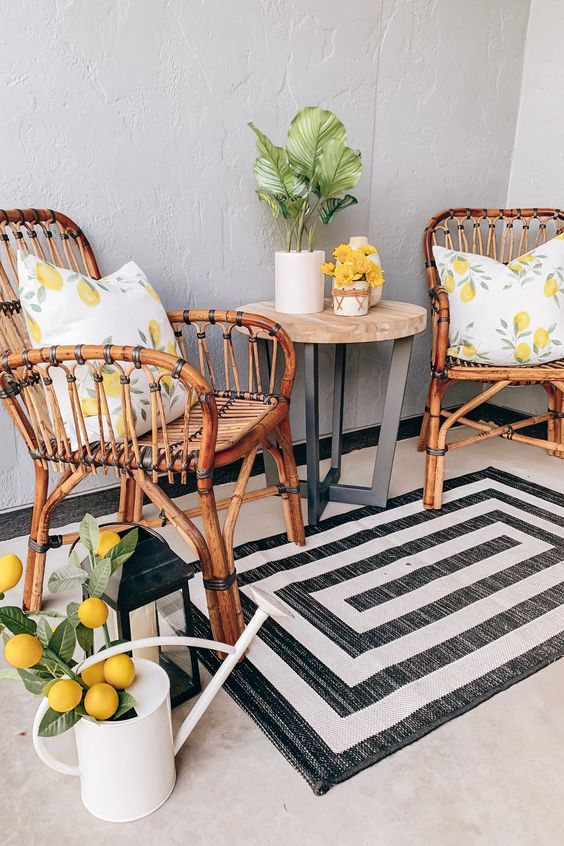 a small outdoor space with rattan chairs, a coffee table, a printed rug, a watering can with fake lemons for a bold touch
