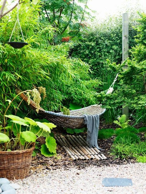 a lush outdoor space with lots of greenery and a living wall, a woven hammock, potted plants and a bamboo mat