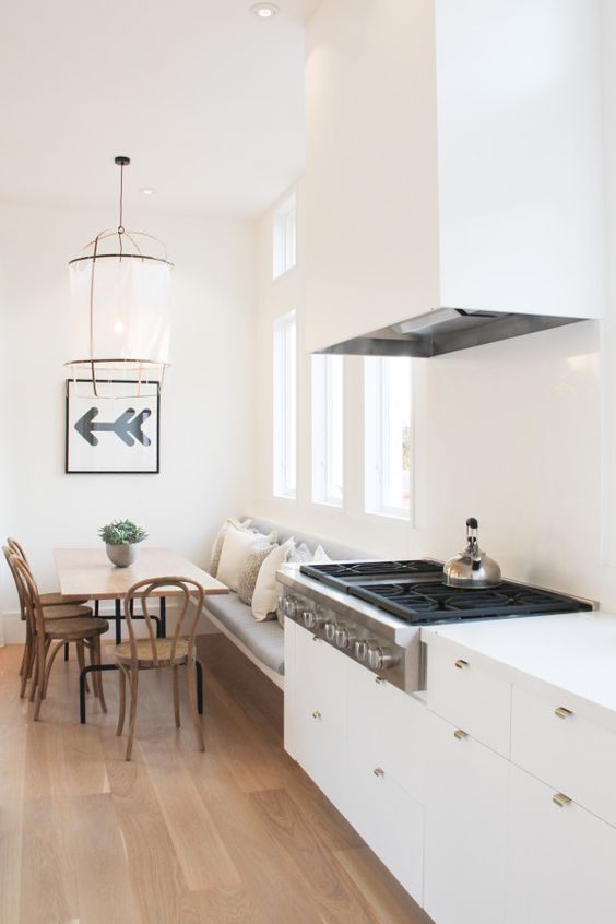 a sleek and minimal white kitchen with a large hood that is hidden in sight - it merges with the wall and brass handles add chic