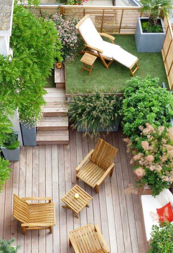 a small modern backyard with a raised platform with grass and a lounger, with potted trees, a ladder and a wooden deck with some wooden furniture